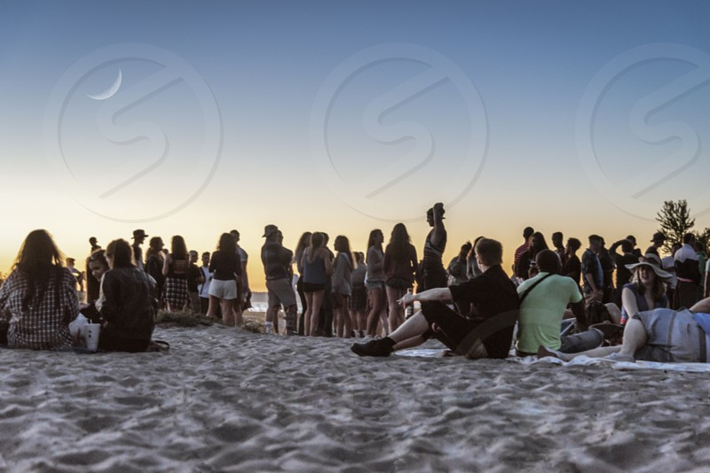 Many people at a beach music festival at sunset with crescent moon. photo