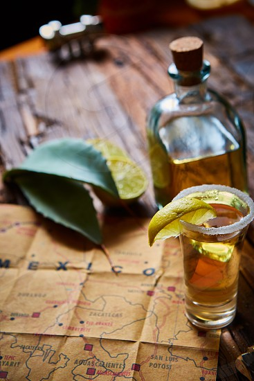 Tequila shot with lime and sea salt on wooden table selective focus photo