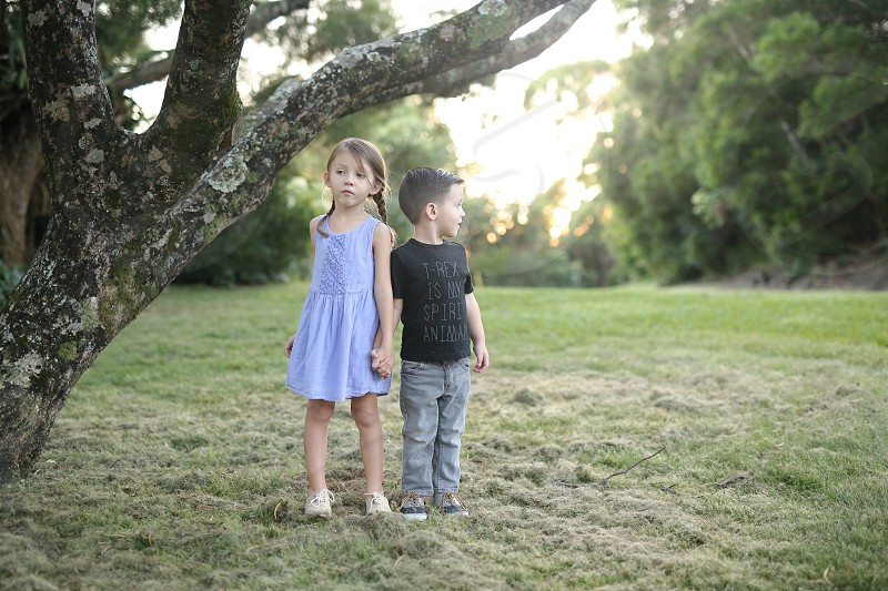girl and boy child holding hands in the park near the black and white tree photo