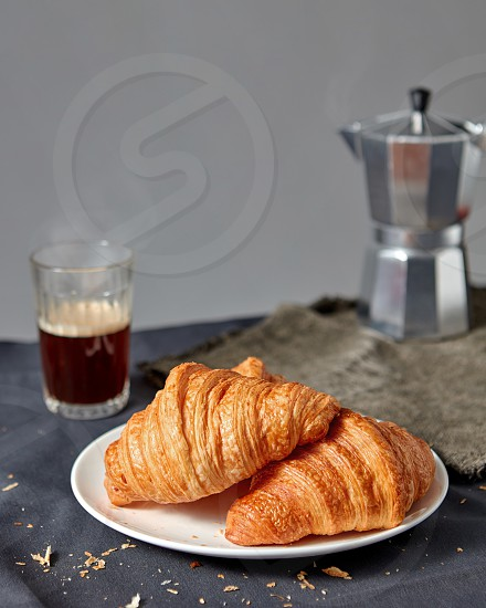 Freshly baked french pastry on a plate with glass of hot aromatic coffee and geyser maker on a dark texile background copy space. photo