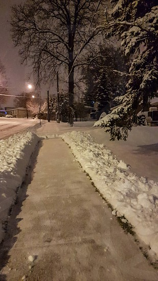 freshly shovelled sidewalk at night with snow still falling photo
