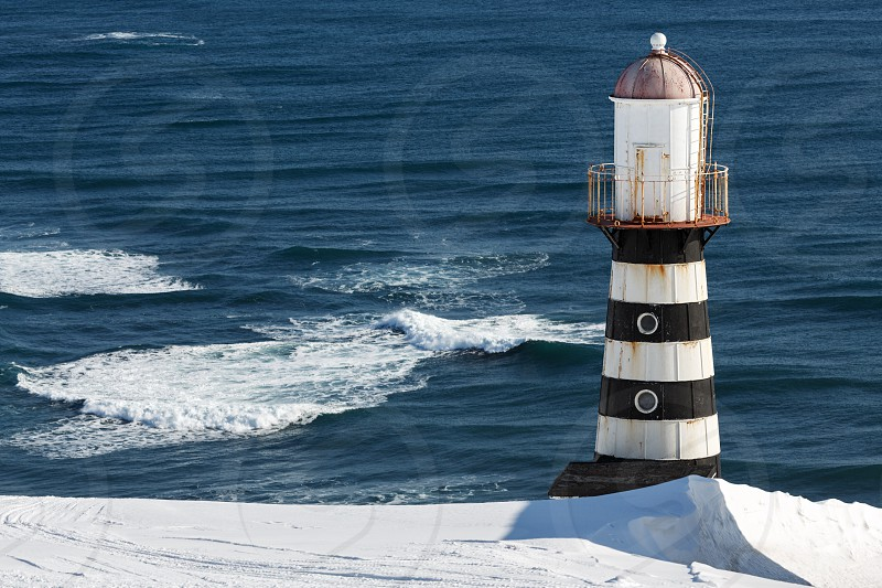 Winter view of lighthouse on coast of Pacific Ocean on a sunny day. Russia Far East Kamchatka Peninsula Petropavlovsk-Kamchatsky. photo