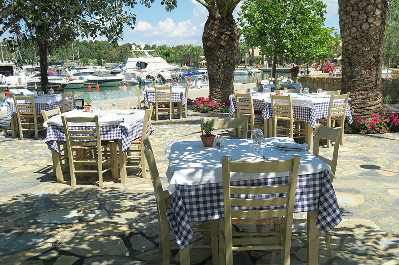 Greek empty taverna chairs and tables by a marina in Greece. A greek tavern by the marina on a summer day at a resort in Halkidiki Greece. photo