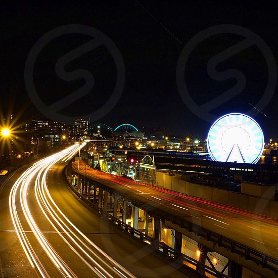 time lapse photography of busy overpass road with ferry's wheel background during nighttime photo