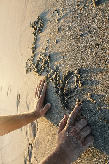 person writing love on sand photo