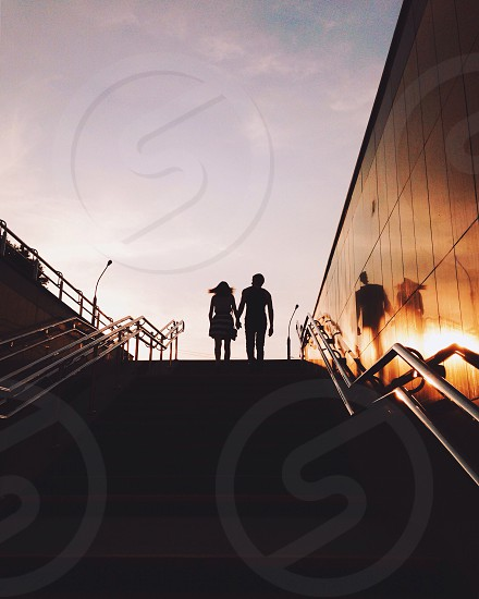 couple walking using stairs while holding hands photo