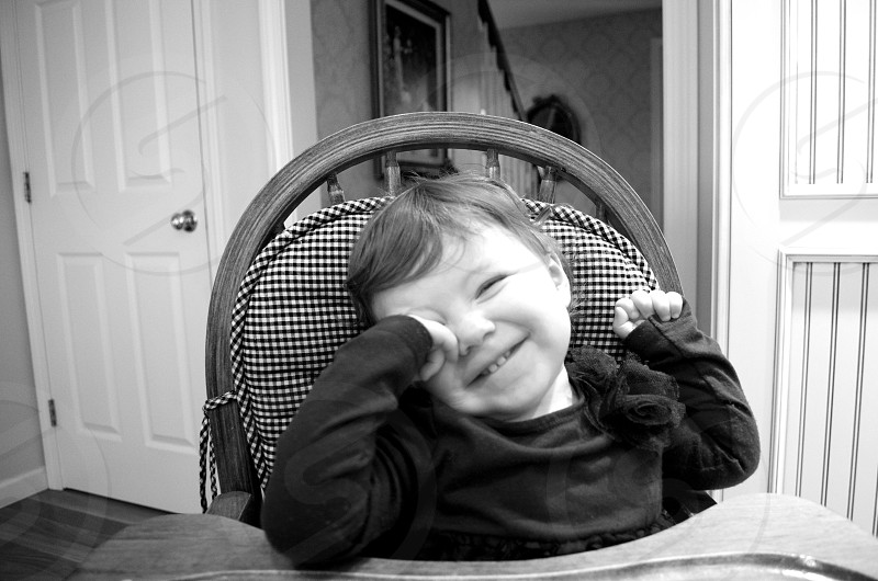 child in black round neck long sleeved shirt sitting on high chair smiling photo