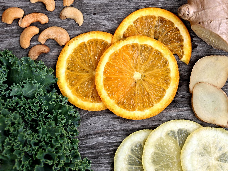 Looking down at oranges and  lemon with kale and cashews photo