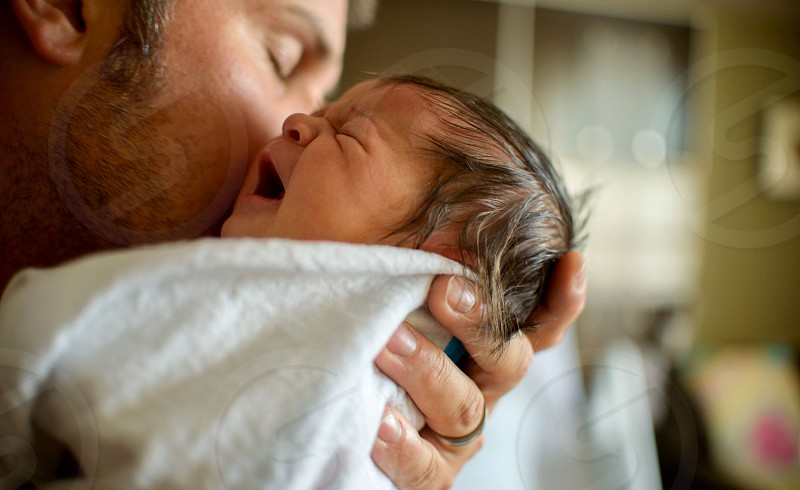 man holding newborn photo