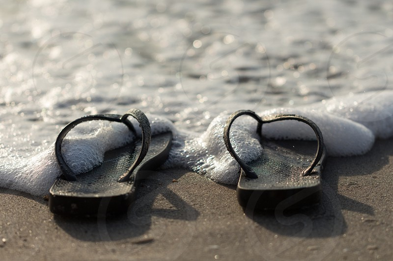 sandals in the sand covered with sea foam photo