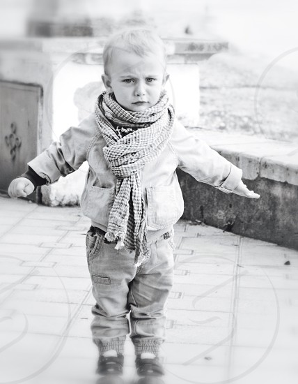 greyscale photography of boy wearing scarf and jacket standing on ground photo