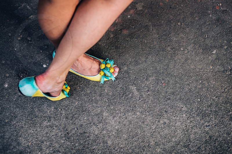 person wearing green and yellow flats with flower accent photo