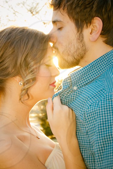 man in green collared shirt kissing woman on forehead with sun raise as background photo
