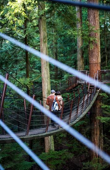 Walking on suspension bridge through the bridge cables couple walking photo