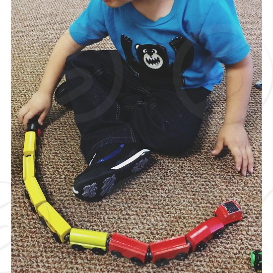 boy in blue t shirt with black bear print paying a toy steam train photo