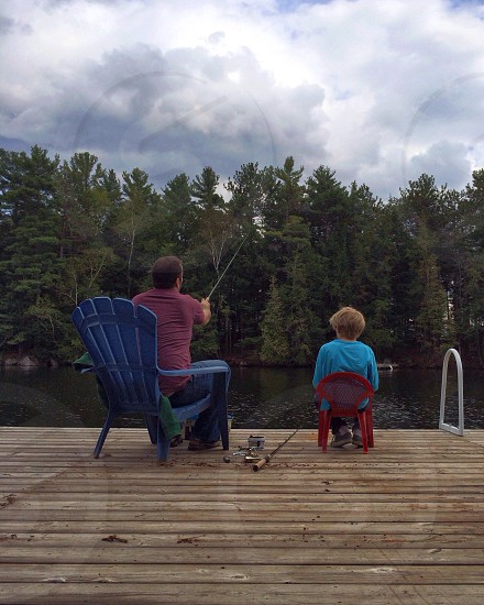 brunet man and blond child sitting on wood deck casting fishing lines photo