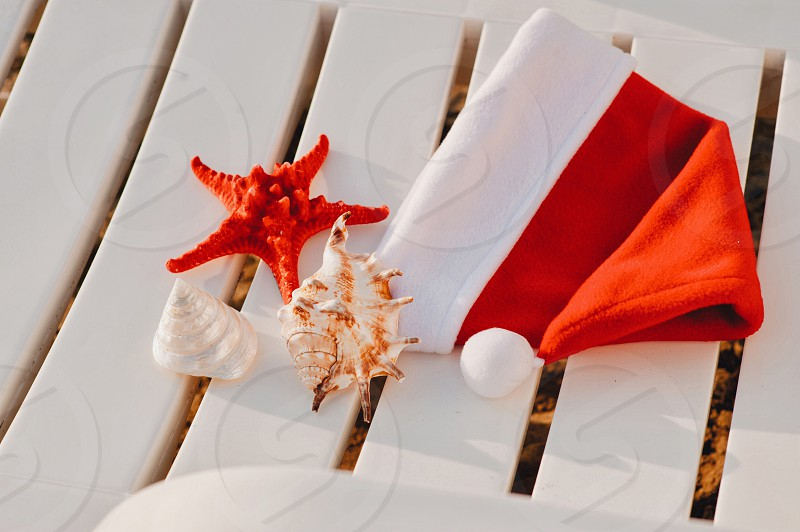 Santa Claus Hat on sunbed near tropical calm beach with turquoise caribbean sea water and white sand. Christmas vacation celebration . Starfish in red santa hat at the seaside. Christmas in summer photo