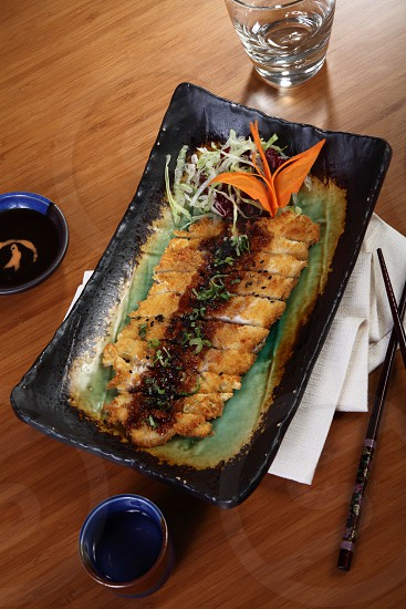 fried sliced tonkatsu in black ceramic rectangular plate on brown wooden table photo