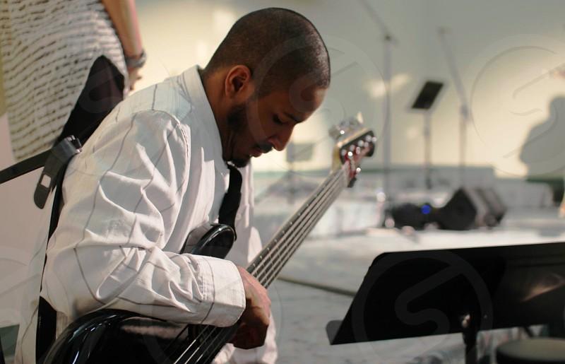 man in white dress shirt sitting white playing bass guitar photo