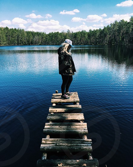 woman wearing black leather jacket and white cap standing on wooden bridge looking at blue calm body of water surrounded by trees under blue and white cloudy sky during daytime photo