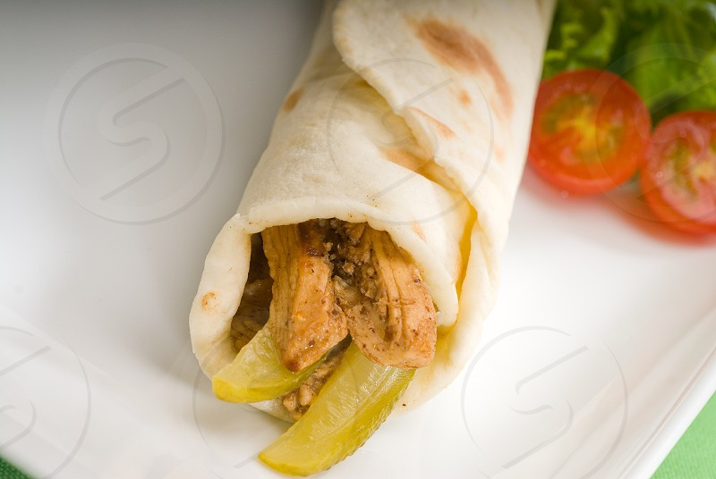 pita bread chicken roll with pickles cucumbers on a plate with pachino tomatoes and lettuce photo