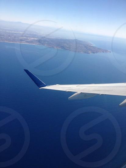 passenger plane flying over body of water photo