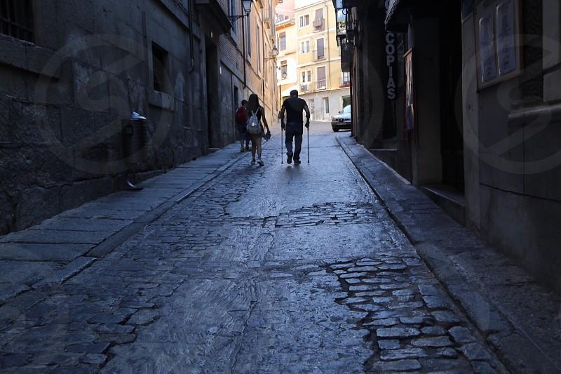 Street photography  backlight  elderly people walking narrow street couple behind nighttime  struggling  photo