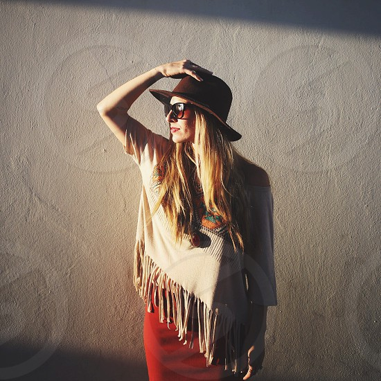 blonde woman wearing a brown hat fringe top and red skirt with her hand on her hat looking towards the sun photo