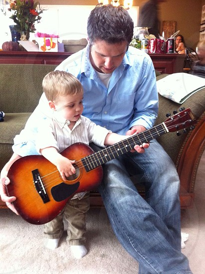 Father son teaching guitar playing learning music photo
