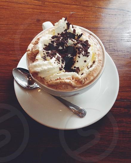hot chocolate in white coffee mug with whipped cream and chocolate shavings photo