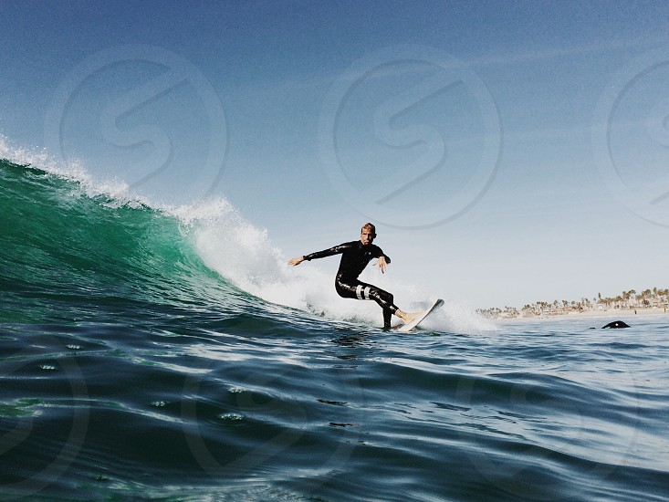 man in black rash guard surfing on sea waves with white surfboard under clear blue sky photo