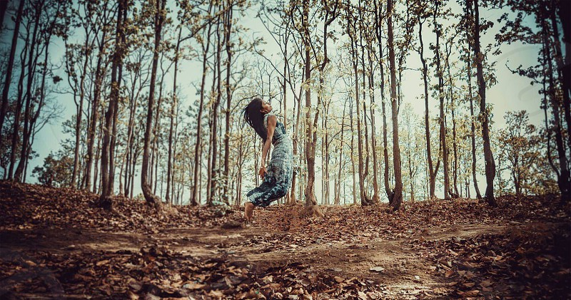 woman doing jumpshot on forest photo