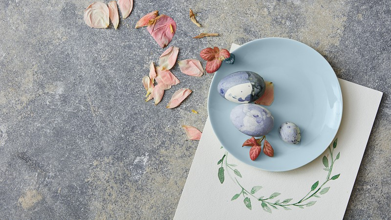 Easter eggs with flowers decoration and paper with watercolor frame on stone background photo