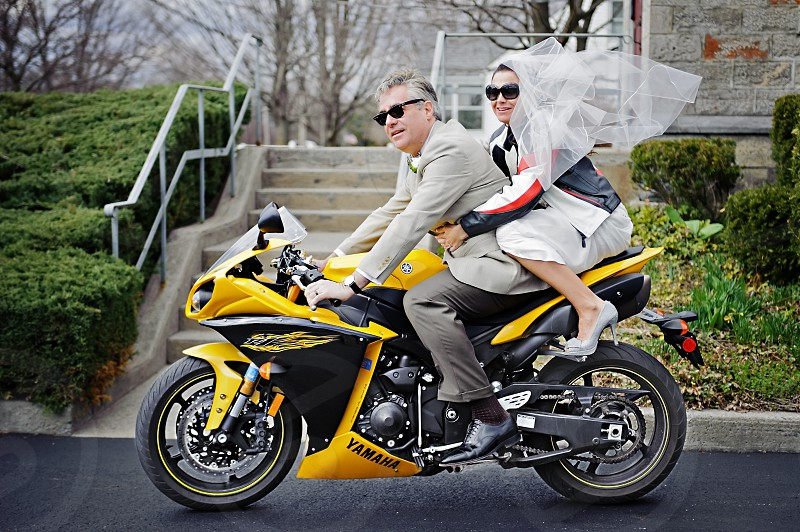 Best friends for life ride away on motorcycle just after their wedding. photo