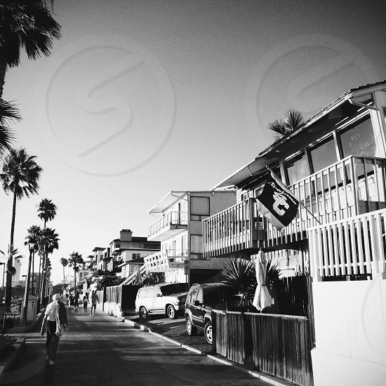 gray scale photo of people walking in sidewalk beside house photo