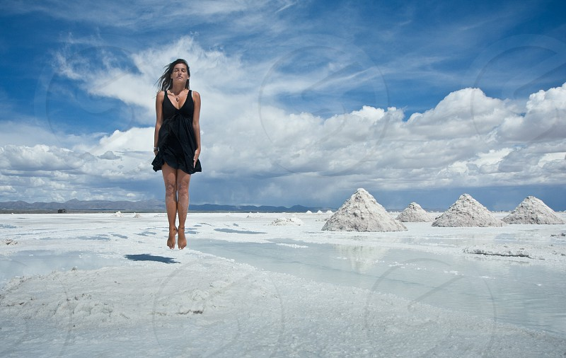 surreal portrait of fashion woman in salt desert in Bolivia photo