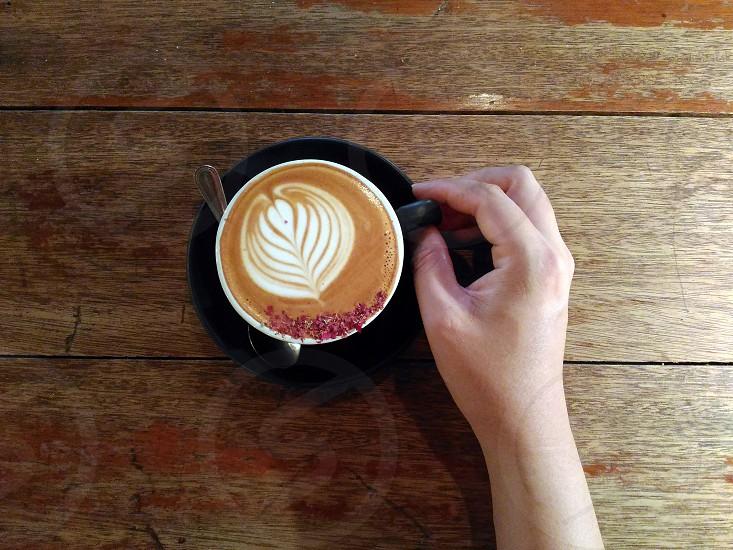 leaf artwork cappuccino in white ceramic mug photo