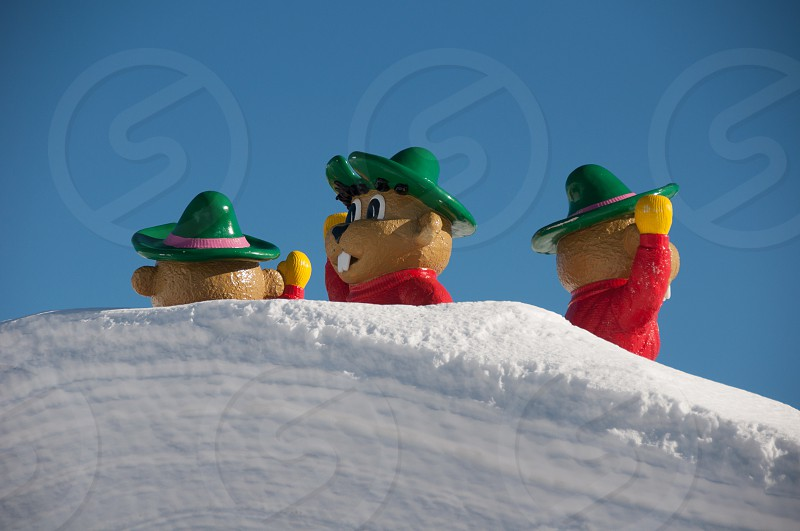 Cartoon characters on the top of a roof nearly covered by snow in a ski report in the Tirol Austria photo
