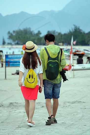 photo of man in green hoodie walking with a woman in pink skit and yellow drawstring bag on a brown sand during daytime photo