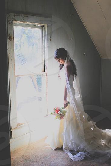 woman in white wedding dress standing near a door photo
