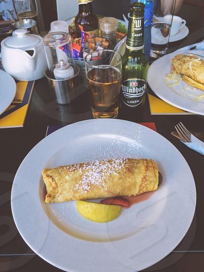 Strawberry Crepe and Windhoek Beer at a Local Pancake Restaurant in South Africa photo