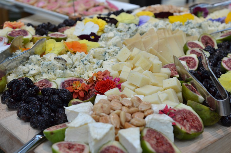 Cheese display fruit display Brie almonds flowers figs blue cheese Munster cheese Swiss cheese photo