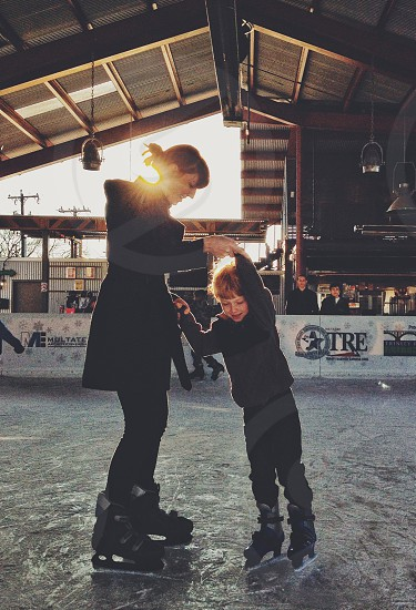 A woman and a little boy ice skating.  photo