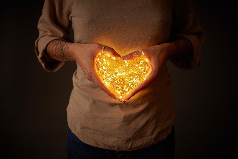 A woman holds the lights in the shape of a heart in the dark. The concept of the Valentine's Day photo
