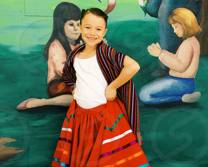 girl in shawl and red skirt standing in front of mural photo