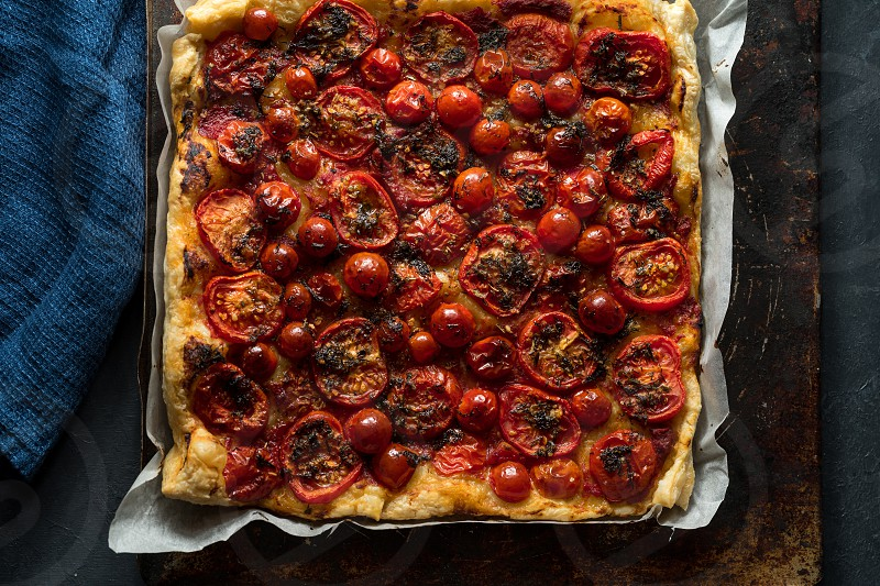Home baked tomato tart on a dark rustic background photo