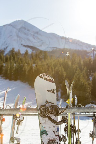 Snowboard and skiis propped up outside the snack bar at Big Sky ski resort Montana.  Horizontal shot also available. photo