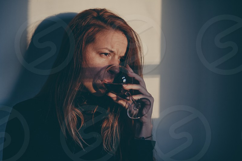 Drunk woman drinking wine alone and depressed photo