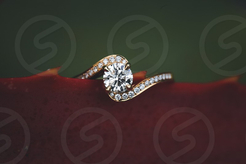 round diamond and yellow gold ring on a burgundy leaf photo