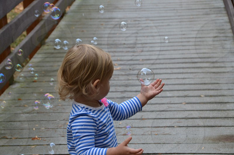 Girl child toddler catching bubbles blue & white striped shirt pink flower photo